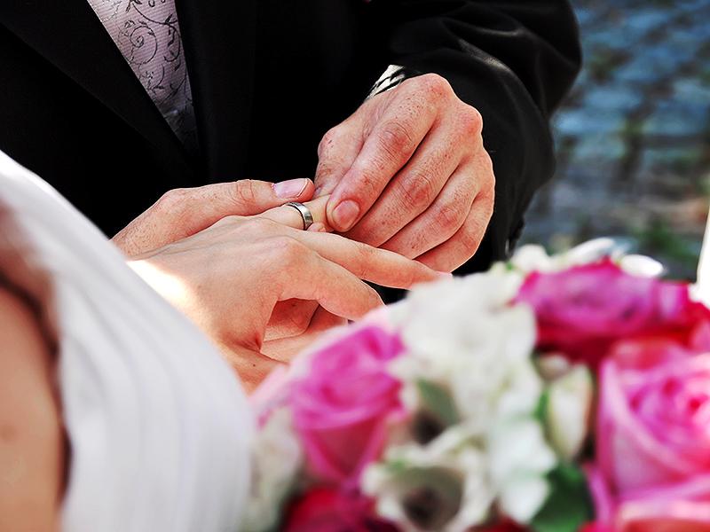 Groom-putting-wedding-band-on-brides-ring-finger